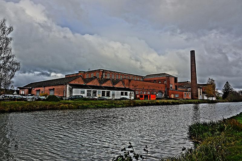 Am Ufer reihen sich die verlassenen und verfallenen Fabrikhallen auf