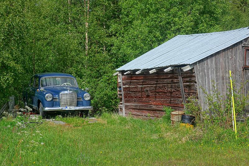 Oldtimer neben einem Holzschuppen