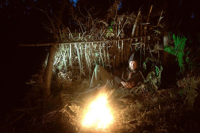 Survivalstar Heiko Gärtner am Lagerfeuer in seinem Lean-To.