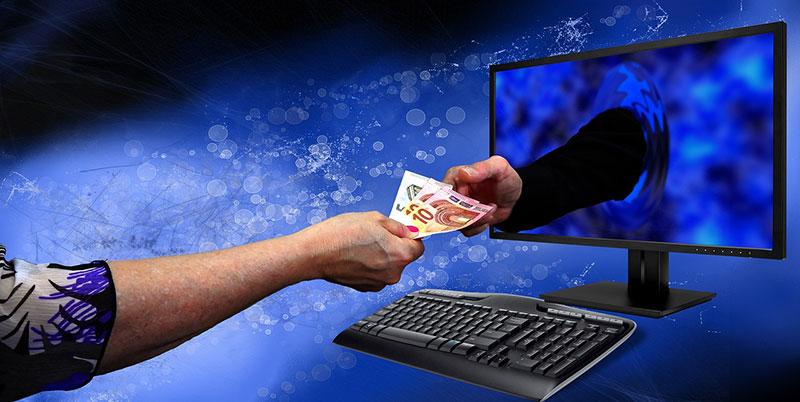 Eine Hand im Monitor nimmt das Geld eines Users an sich.